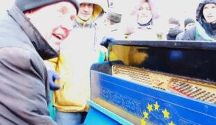 Ucrania: un hombre protesta tocando el piano ante la policía antidisturbios