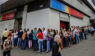Venezolanos hacen largas colas para cambiar billetes de 100 bolívares