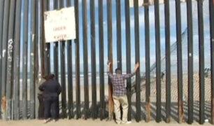 Pareja se saluda a través de valla fronteriza entre México y Estados Unidos