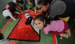 Niños forman camiseta de Paolo Guerrero con tapas recicladas