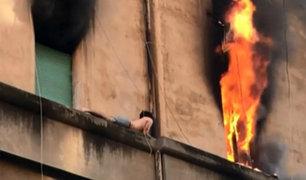 Italia: rescatan a joven en cornisa cuando escapaba de incendio