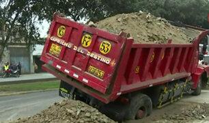 SJL: camión de carga se hunde en pista y rompe tubería de agua