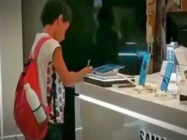 Captan a niño usando tablet de exhibición para terminar su tarea