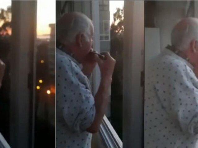Hombre de 80 años toca la armónica mientras vecinos aplauden