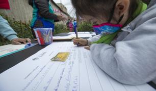 Adultos y niños firman libro del Bicentenario de la Independencia